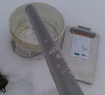 Emptying snow cores into bucket to be weighed