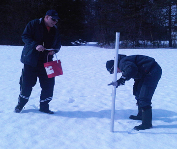 Staff measuring snow depth